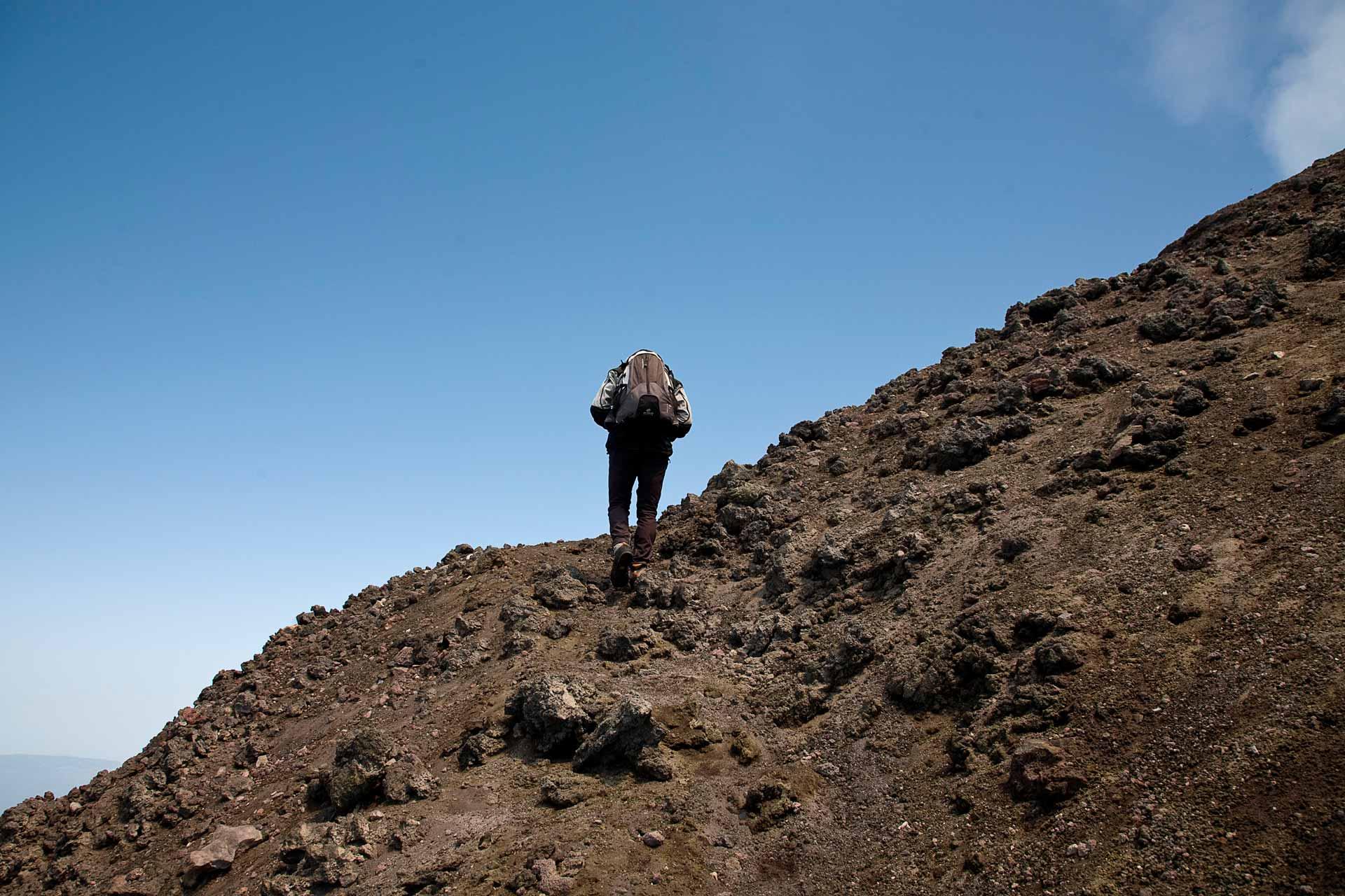 Continuiamo la salita sul costone sud-ovest del vulcano, i coni neri dei crateri avventizi, che incontriamo lungo il percorso, sono le sinistre vestigia di terribili e recenti eruzioni laterali. L'area craterica sommitale non rimane mai uguale nel tempo, anzi, si trasforma continuamente. Basti pensare che solo centoventi anni fa la cima del vulcano culminava con un unico Cratere Centrale, mentre oggi ne troviamo ben quattro, a riprova di rapidi e marcati cambiamenti morfo-strutturali.