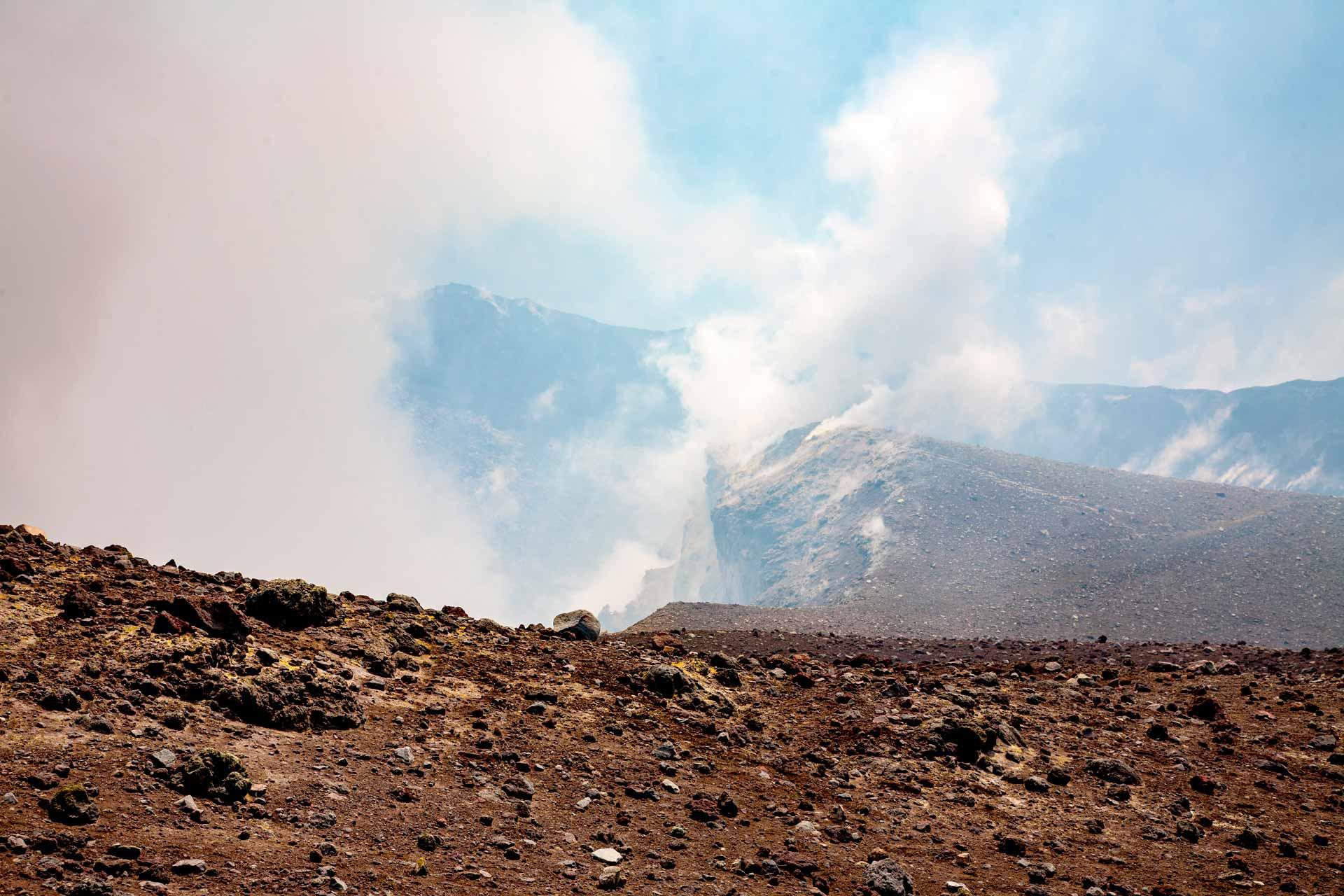 """Proseguendo in un'atmosfera minacciosa di nubi mefitiche, si apre sul versante ovest, un baratro spaventoso: la """"Bocca nuova"""". Oggi sempre attivo, il cratere si ingrandisce ancora. Il suo pozzo di 300 mt di larghezza, racchiude nelle sue profondità fumose, molte bocche eruttive."""