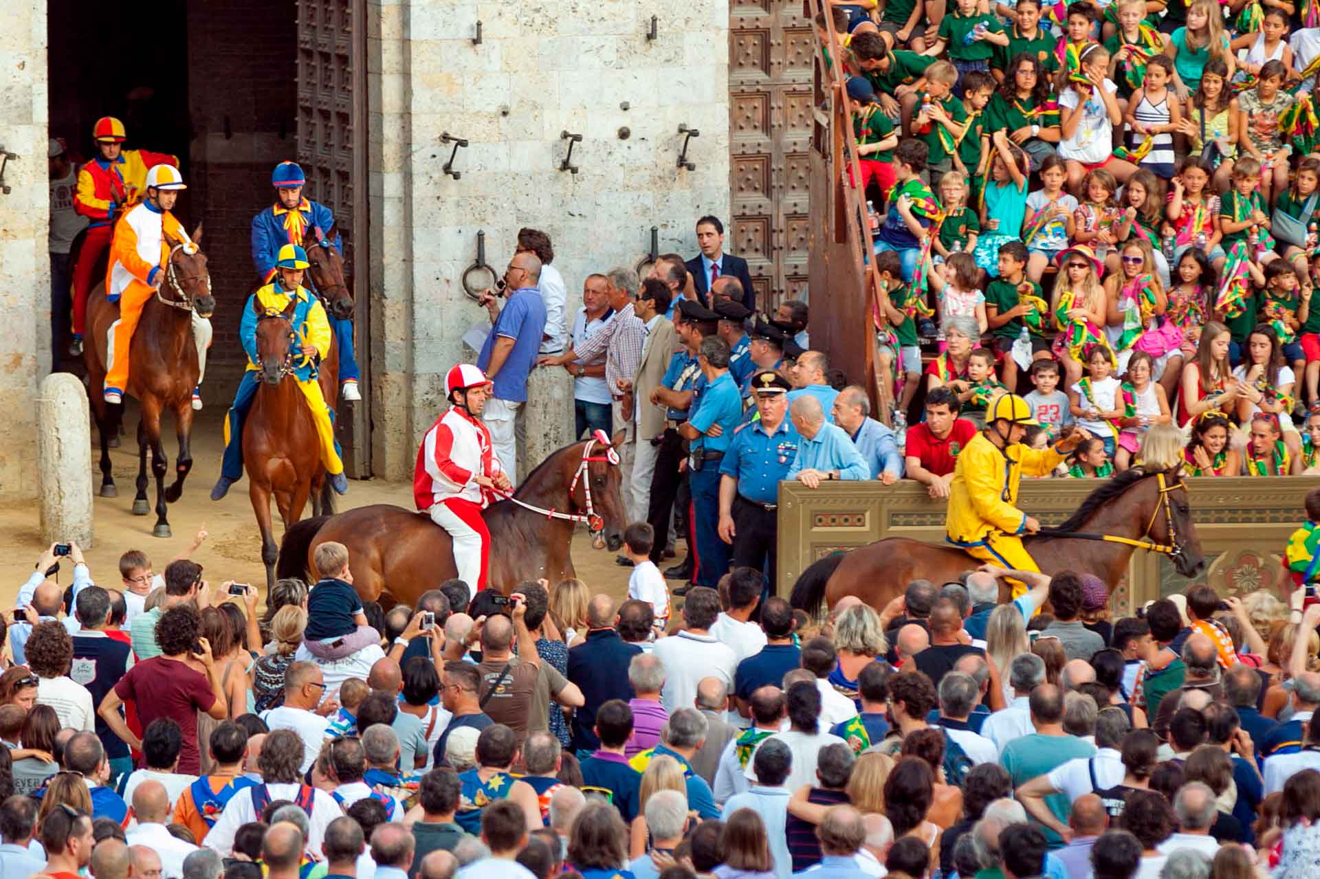 LA PRIMA PROVA - L'uscita dei cavalli, montati dai fantini delle dieci contrade, dal Cortile del Podestà è annunciata alla Piazza, per ogni singola prova, da un rullo di tamburo e dallo scoppio di un mortaretto.